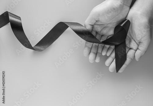 Fotografija Hand holding Black ribbon on black and white tone with copy space, symbol of Skin Cancer awareness month on May, Melanoma cancer, Mourning ribbon symbolic