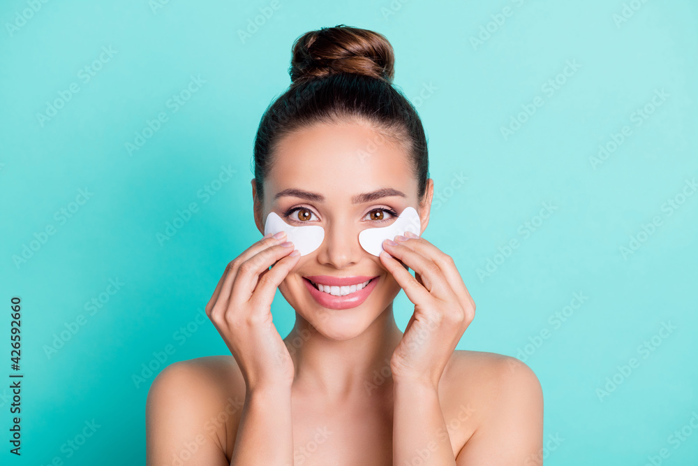 Fototapeta Portrait of attractive trendy cheerful girl applying patches enhancement freshness isolated over bright teal turquoise color background