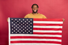 Smiled Black Muscular Bearded Man Holding American Usa Flag In Front Of Him, Wearing A Mustard T-shirt, Standing Indoor Over Red Background, Shows Its Independence And The Rights Of An Equal Person