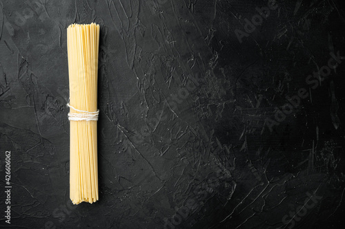 Fotografie, Obraz Wholemeal spaghetti ,Yellow long uncooked dried pasta, on black stone background