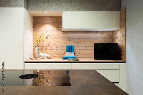Fotografija modern island stove, integrated extractor hood and wood look niche with decorati