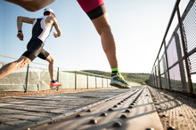 Triathlon Runners Compete On A Bridge In Wide Angle Image