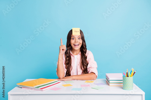 Portrait of funny girl finger direct up unbelievable reaction sitting in classroom isolated on blue color background