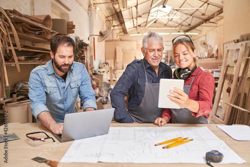 Billede på lærred Craftsmen team with computer in the joinery