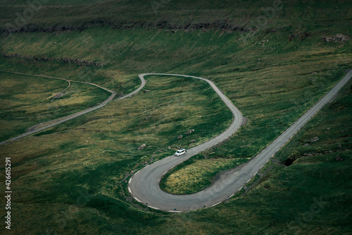 Fotografija White campervan on a scenic winding pass road in grassland on Faroe Islands