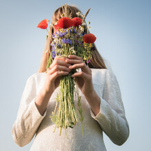 Conceptual Portrait Of Girl In White Dress Or Bride Holding Summer Bouquet Of Wild Flowers Hiding Her Face