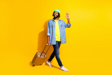 Full Size Photo Of Young Cheerful Smiling Afro Man Walk With Baggage Hold Hand Saying Hello Isolated On Yellow Color Background