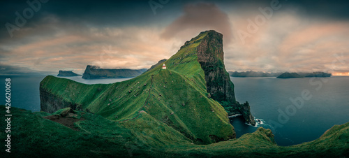 Fotografia, Obraz Panorama at Lighthouse with steep cliffs during sunset on Faroese island Kalsoy, Faroe Islands