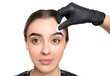 Leinwandbild Motiv Beautician wiping tint from woman's eyebrows on white background, closeup