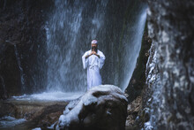 Man In Traditional Japanese Shugendo Outfit Doing Waterfall Meditation In Winter With Ice And Snow