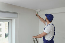 Handyman Painting Ceiling With White Dye Indoors, Space For Text