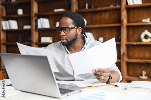 Foto Clever and concentrated African-American guy is doing paperwork, a man looking t