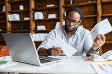 Worried African-American Looking Through Correspondence, A Guy Holds Envelopes In Hands, Got Fine By Post, Concentrated Man Sitting At The Desk With A Laptop In Contemporary Office