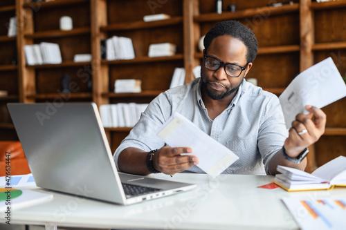 Billede på lærred Worried African-American looking through correspondence, a guy holds envelopes i