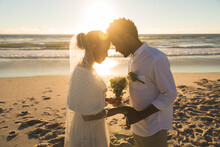Happy African American Couple In Love Getting Married, Touching Foreheads On Beach During Sunset
