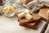Composition with fresh bread and butter on light background, closeup