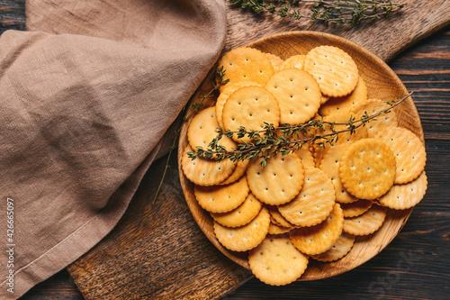 Fototapeta Plate of crackers on wooden background obraz