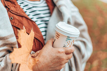 Fall Season. Caucasian Woman Holding Hand With Autumn Maple Leaf And Paper Cup With Hot Drink. Lady In Warm Wool Blanket In The Fall Season
