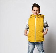 Teenage Boy In A Yellow In Puffer Waistcoat, Sleeveless Down Jacket With A Zipper And Jeans. On White Background