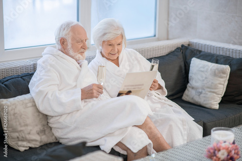 Valokuvatapetti Senior couple in white robes having great times in spa salon and looking relaxed