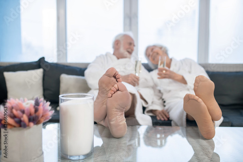 Valokuva Senior couple in white robes having great times in spa salon and looking relaxed
