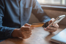 Male Businessman Use Credit Cards To Conduct Financial Transactions Through Phones And Laptop.