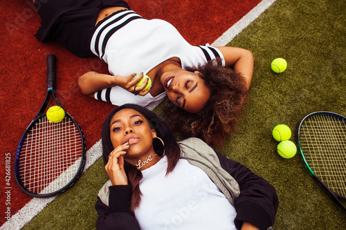 young pretty girlfriends hanging on tennis court, fashion stylish dressed swag, best friends happy smiling together - fototapety na wymiar