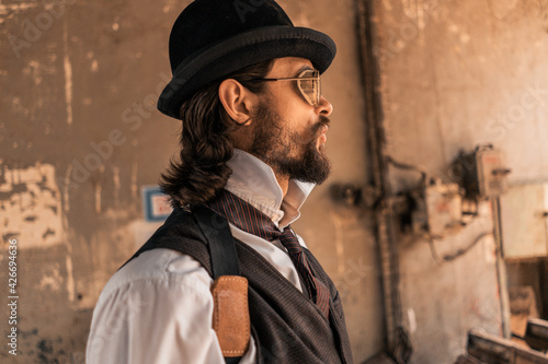 Fototapeta Steampunk. A hero on a river barge surrounded by steel mechanisms. A man with a weapon. obraz