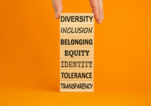Diversity Belonging Inclusion Equity Identity Tolerance Transparency Words Written On Wooden Block. Male Hand. Beautiful Orange Background. Diversity, Inclusion And Belonging Concept.