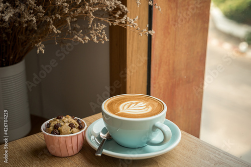 Obraz Hot coffee latte with latte art milk foam in cup mug and Homemade Banana cup cake on wood desk on top view. As breakfast In a coffee shop at the cafe,during business work concept - fototapety do salonu