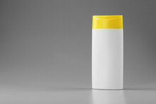 White Plastic Bottle With Yellow Cap With Shampoo Gel On Gray Background