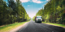 Truck, Tractor Unit, Prime Mover, Traction Unit In Motion On Country Road Through Forest, Freeway. Cloudy Sky Above Asphalt Motorway, Highway. Business Transportation