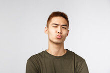 People, Different Expressions And Lifestyle Concept. Close-up Portrait Of Funny Silly, Handsome Young Guy Pouting, Folding Lips And Sending Kiss, Wink Camera, Standing Romantic Over Grey Background