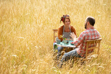 Couple Talking And Eating Berries At Table In Sunny Tall Grass
