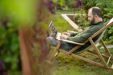 Man Working At Laptop In Lawn Chair In Summer Garden