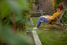 Woman Working At Laptop In Lawn Chair In Summer Garden