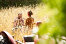 Couple Toasting Water Glasses In Sunny Tall Grass Behind Tractor