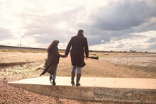 Couple In Winter Coats Holding Hands Walking On Sunny Beach