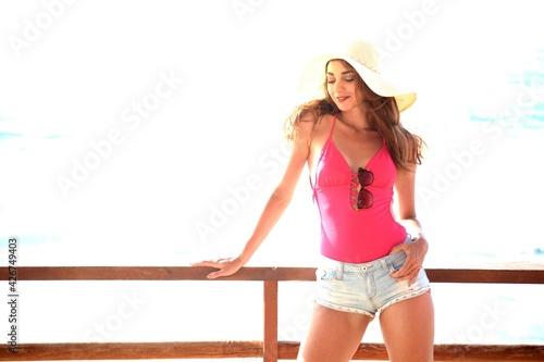 Canvas Plan américain de Jeune femme brune avec chapeau, maillot de bain rose et mini s
