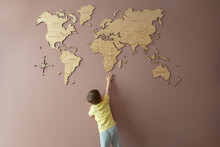 Little Boy Trying To Get Hold Of A Wooden World Map On The Wall