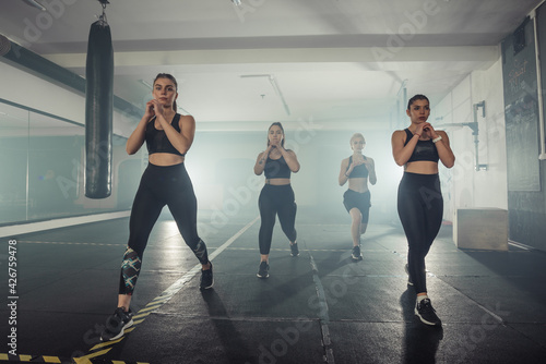 Tablou Canvas Group of sportswomen in sportswear doing lunge exercise at the gym with their ri