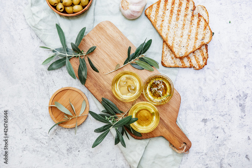 Fototapeta Olive Oil. Organic olive oil in bowl with green olives, herbs, spices and ciabatta bread on white background , banner, healthy mediterranean food concept... obraz na płótnie