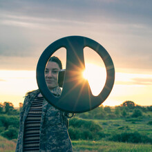 Girl With A Metal Detector On The Background Of A Beautiful Sunset, In A Field Looking For Old Relics And Coins