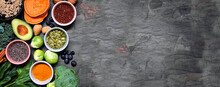 Group Of Healthy Food Ingredients. Top View Side Border On A Slate Banner Background. Copy Space. Super Food Concept With Green Vegetables, Berries, Whole Grains, Seeds, Spices And Nutritious Items.
