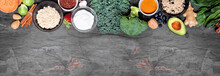 Set Of Healthy Food Ingredients. Above View Top Border On A Slate Banner Background. Copy Space. Super Food Concept With Green Vegetables, Berries, Whole Grains, Seeds, Spices And Nutritious Items.