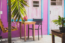 Pink And Blue Patio In Mexico With Wooden Seats And A Swing Chair
