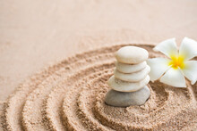 Japanese Zen Garden Stone On Sand Beach. Rock Or Pebbles With Plumeria Flowers With Copy Space. For Aroma Therapy Spa On Summer Holidays. Meditation Wellness And Tranquility Japanese Concept.