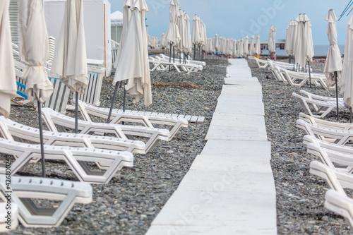 Obraz na plátně Sun loungers on a pebble beach