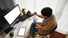 Above View Of Young Man Sitting In Front Of Computer With His Cat And Holding Notebook.