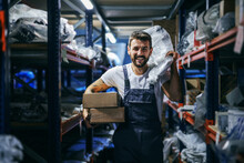 Smiling Bearded Tattooed Hardworking Blue Collar Worker In Overalls Holding Boxes And Bag And Relocating Them While Walking In Storage Of Import And Export Firm.